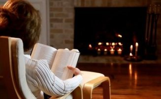 by the fire woman reading